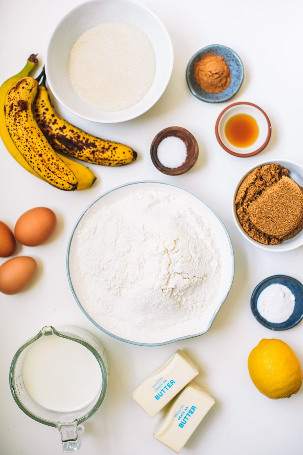 Ingredients for caramel and banana cake spread out on white countertop.