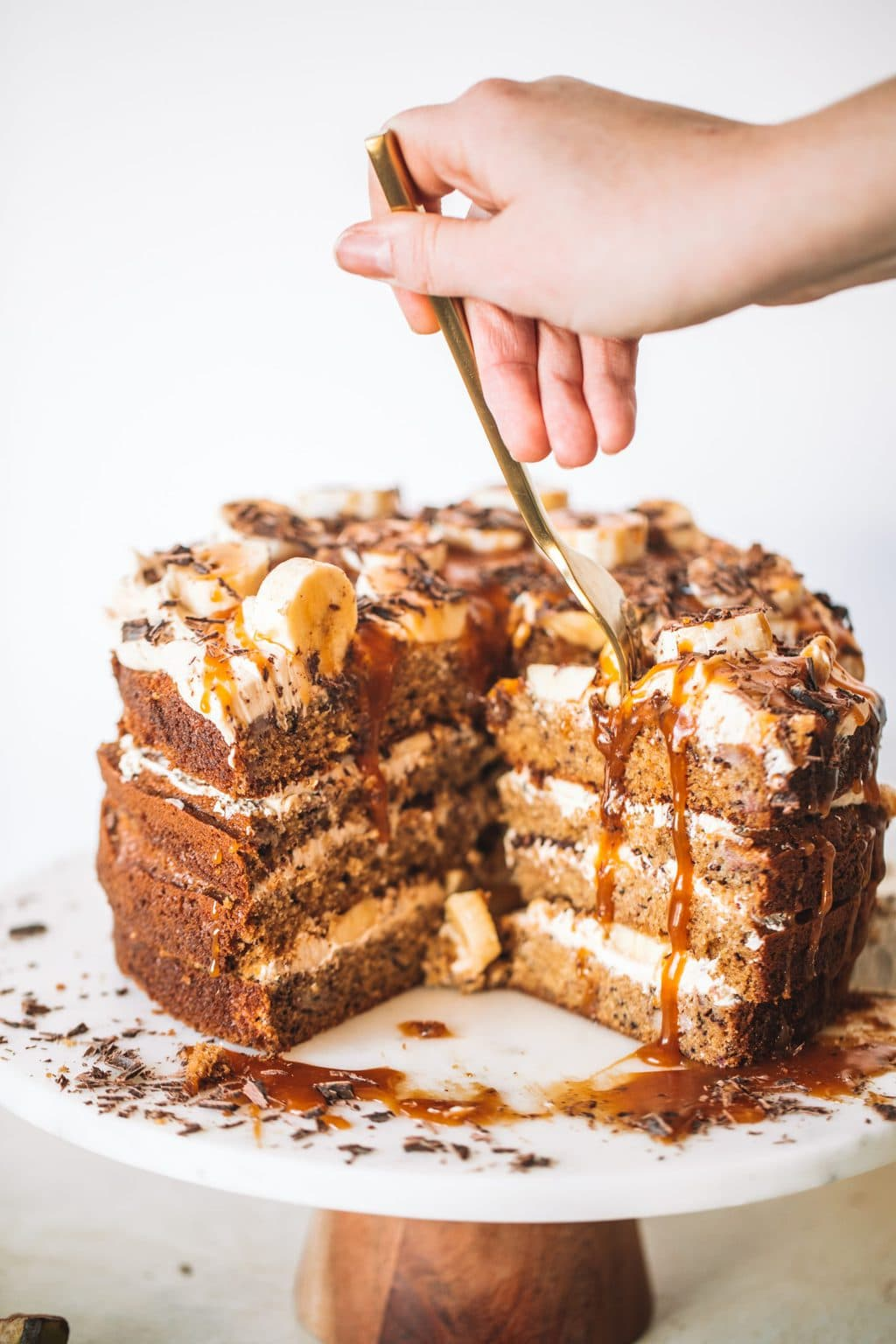 Woman putting fork into banana caramel cake with slices cut out.