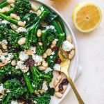 Top shot of broccolini salad with dried cranberries and white beans on plate next to gold fork and sliced lemon.