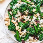 Top shot of broccolini salad with crumbled cheese, toasted almonds and white peans on round white plate.