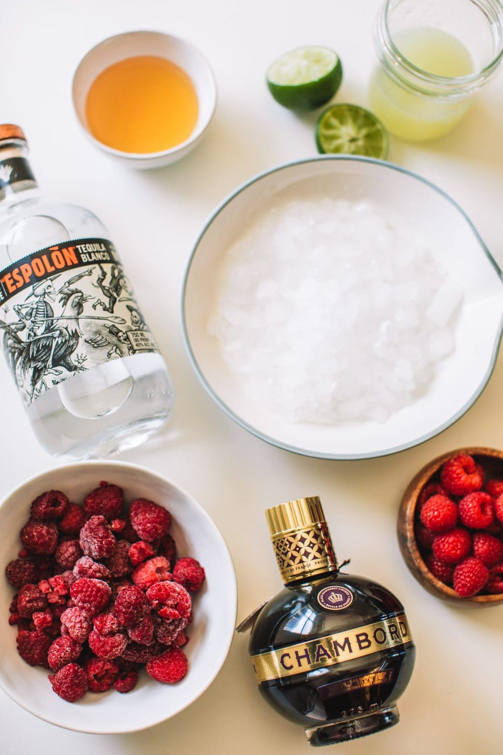 Silver tequila bottle, agave, frozen raspberries, ice, lime juice, chambord and fresh raspberries.