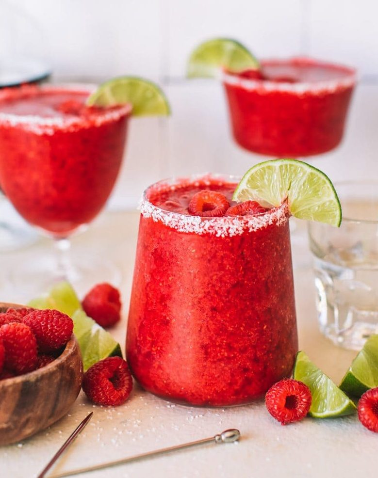 Three frozen raspberry margaritas garnished with a lime wedge and fresh raspberries.