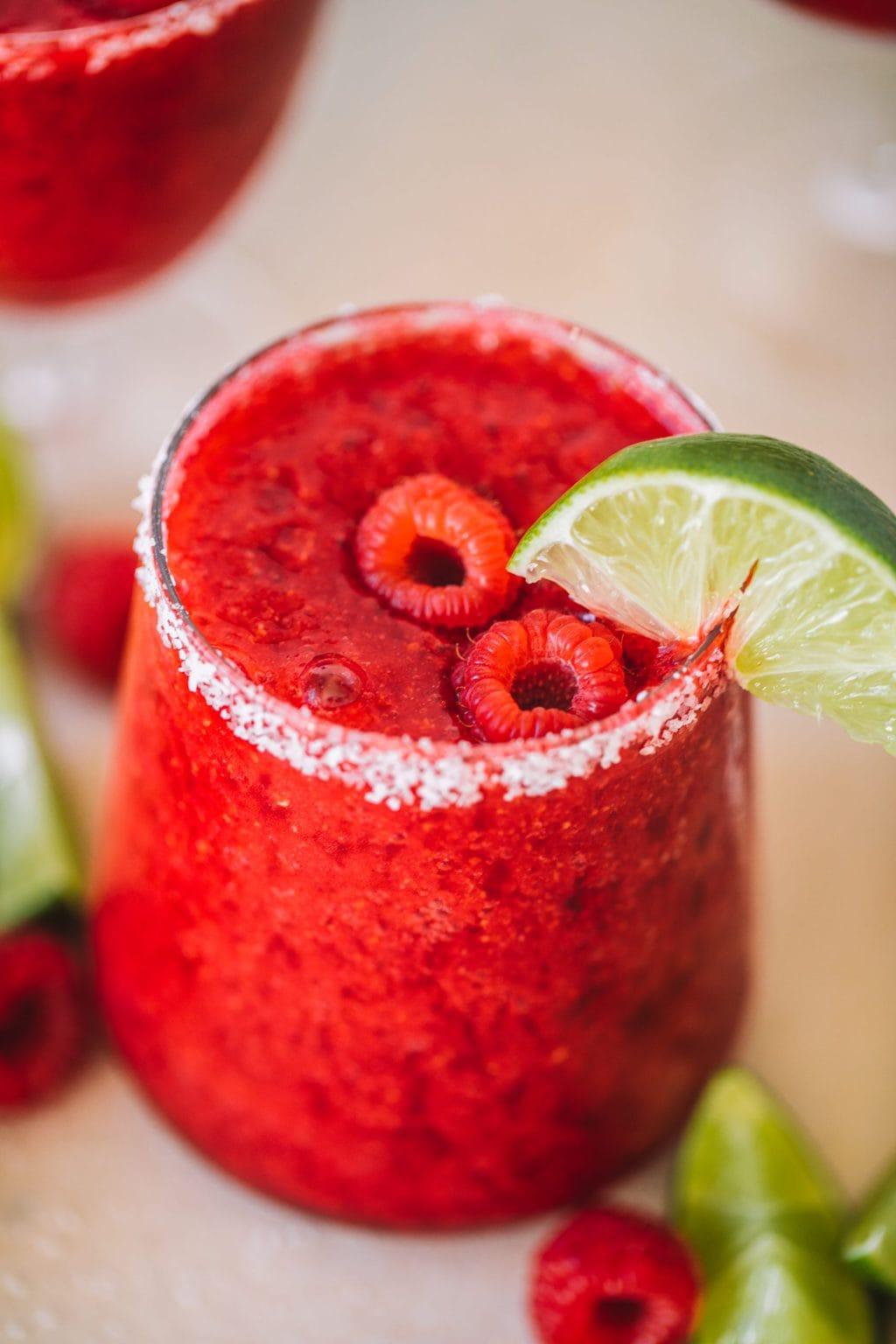 Frozen raspberry margarita with fresh raspberries and a lime wedge.