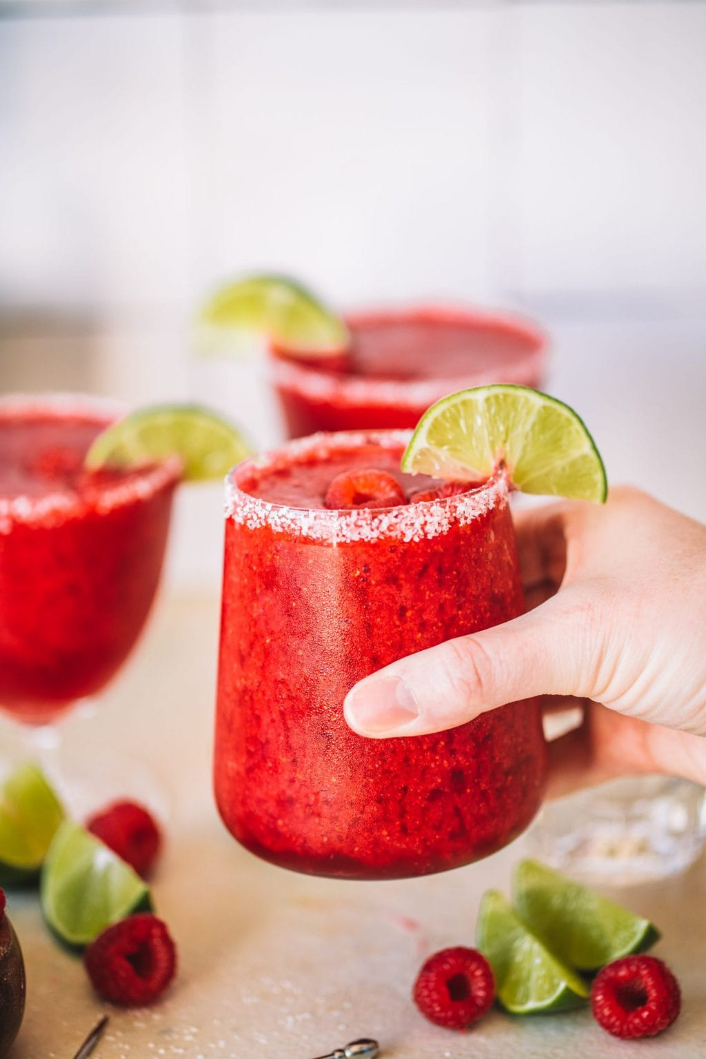 Holding a frozen raspberry margarita with a salted rim.