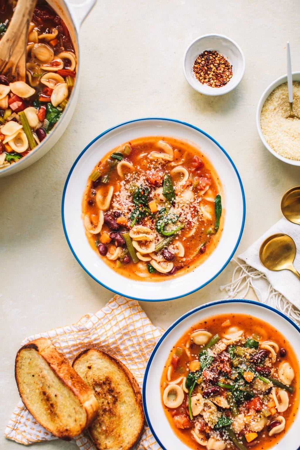 Top shot of two bowls of Minestrone Soup Olive Garden Style next to slices of toast.