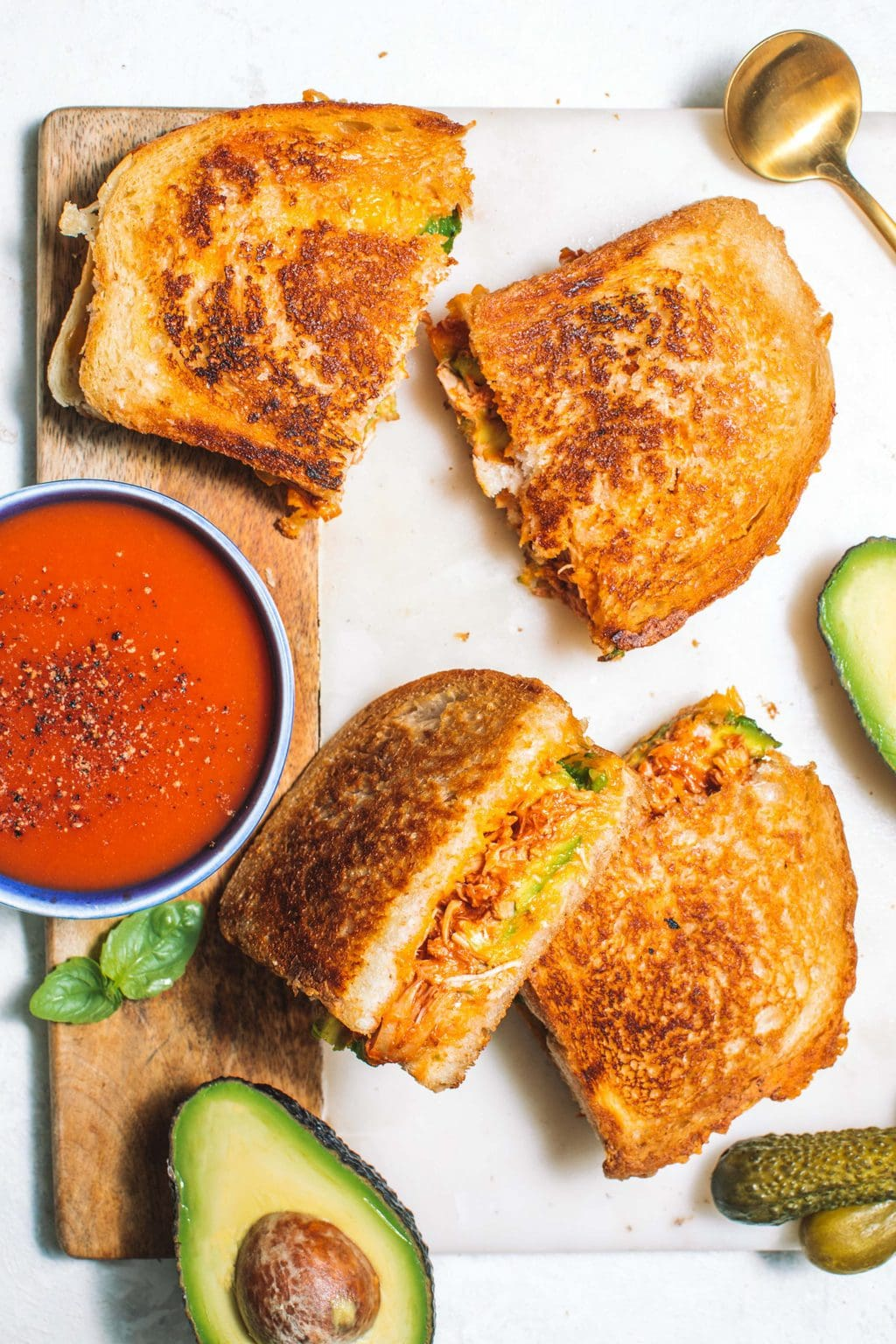 Chipotle chicken avocado melt slices served with tomato soup and pickles.