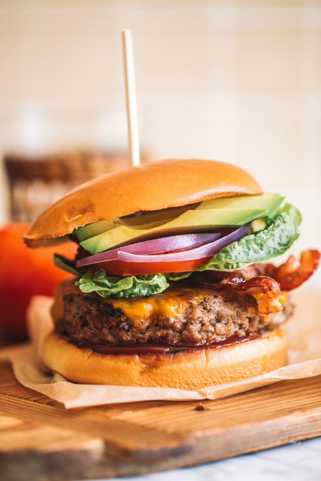 Avocado bacon burger served on a wooden board with a skewer.