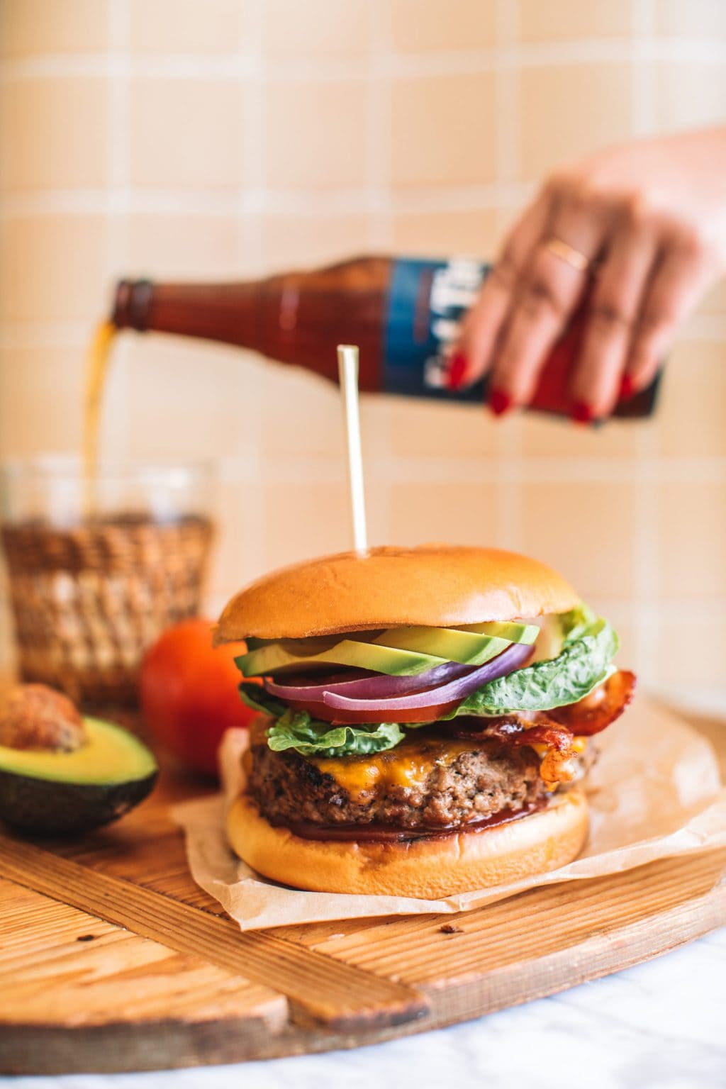 An avocado bacon burger served with a cold beer.
