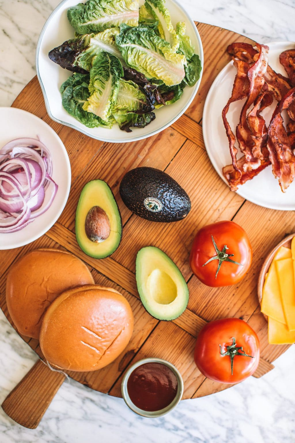 Red onions, lettuce leaves, crispy bacon, brioche buns, halved avocados, tomatoes and cheddar cheese slices.