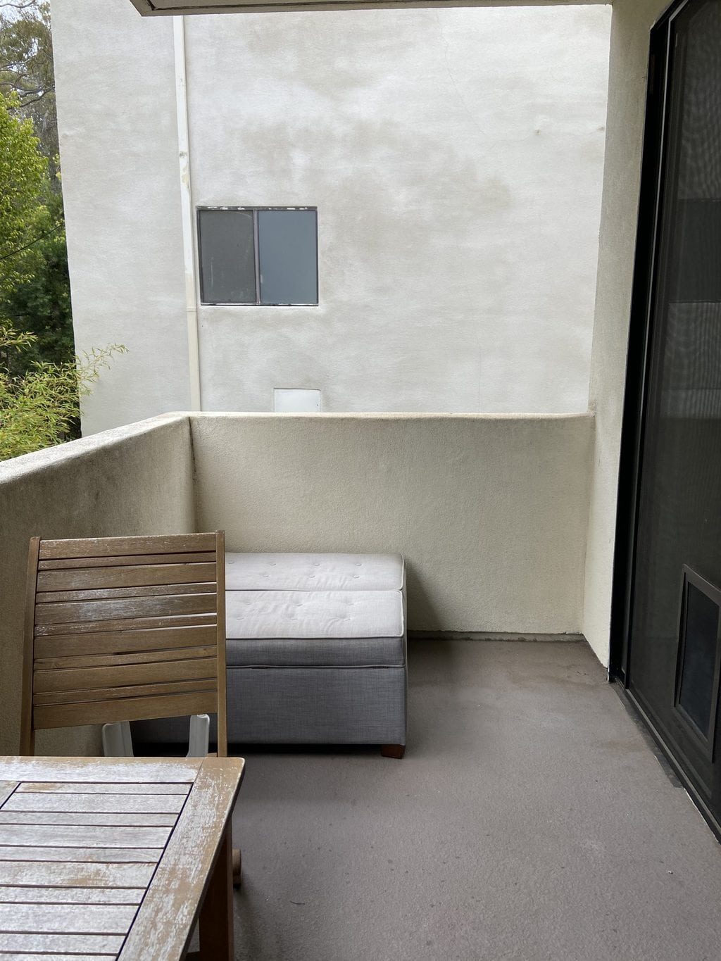 The before side of the lounge area of the patio with a small grey bench.