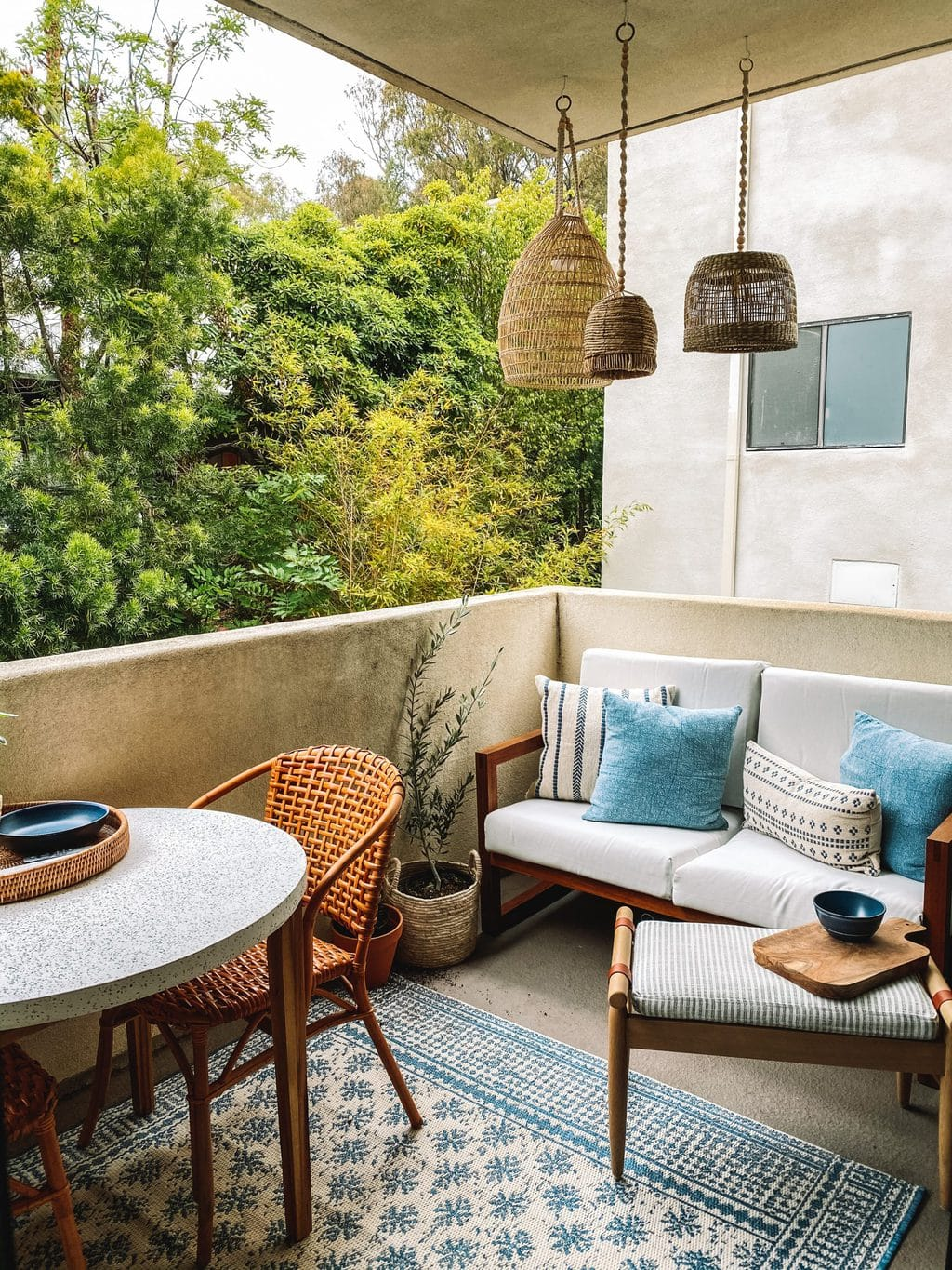 Lounge side of a patio makeover with basket lanterns, a love seat and foot stool.