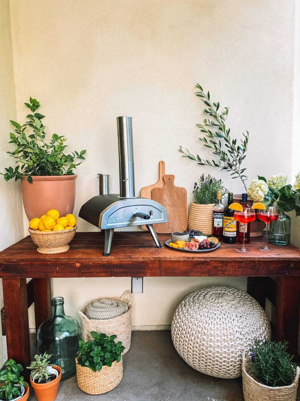 Pizza oven table with a wood fired pizza oven, plants, cutting boards, aperol spritz, and a cheese board.