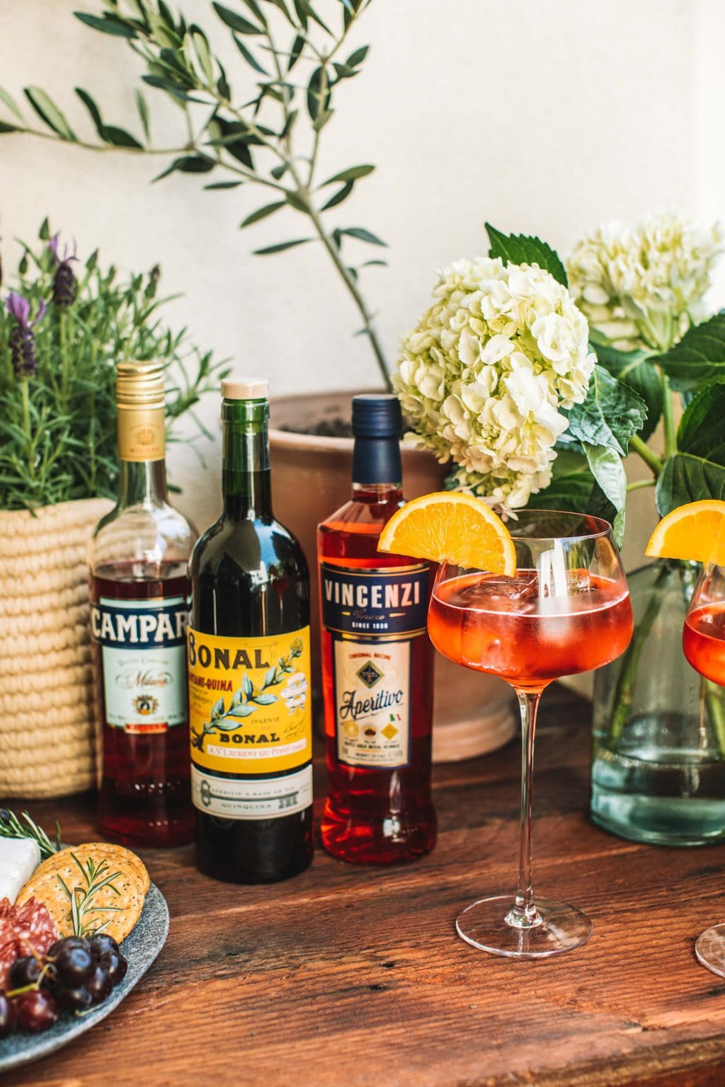 On the wooden pizza table are three different bottles of aperol and a glass made with an aperol spritz.