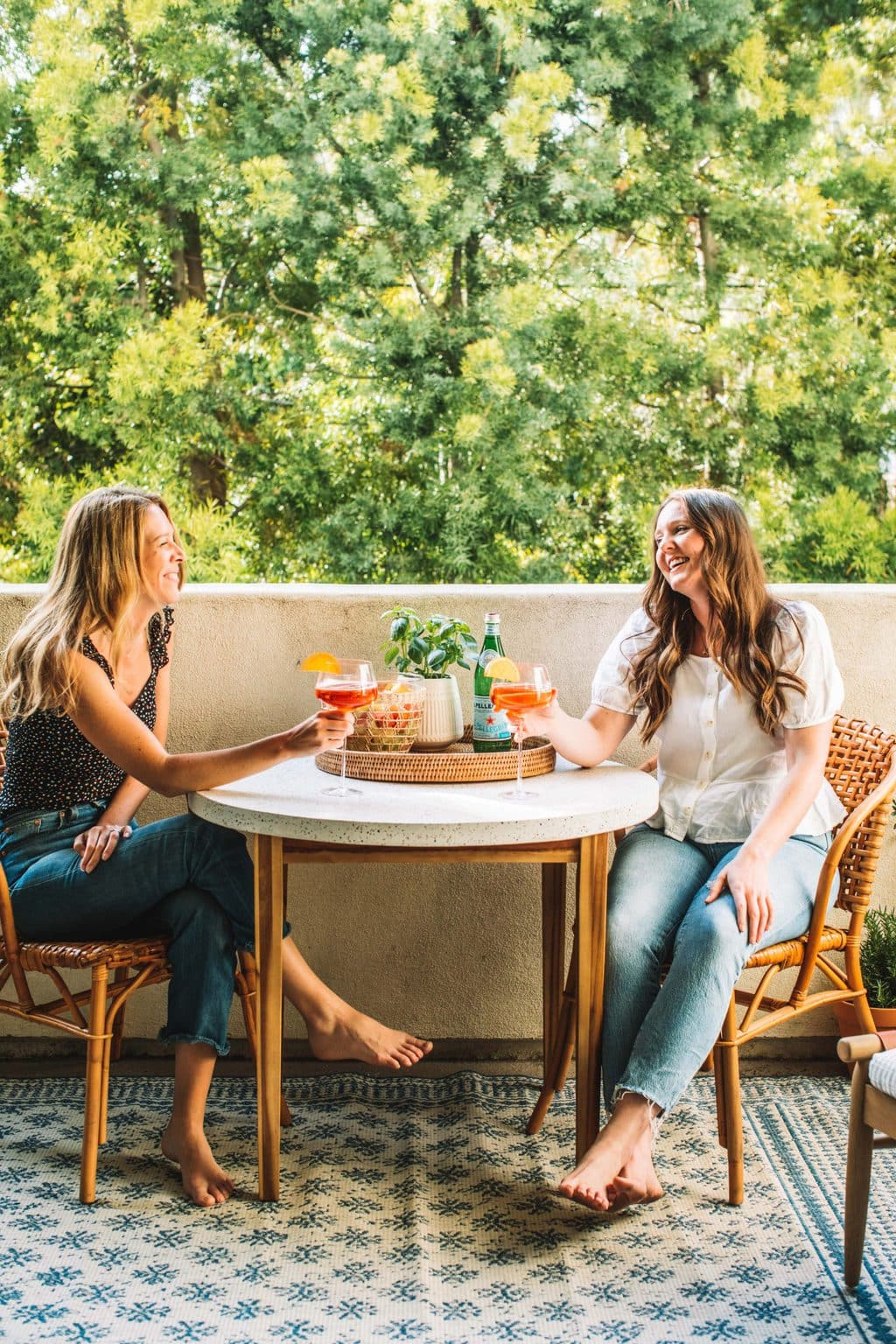Two girls enjoying a cocktail on an outdoor dining table set.
