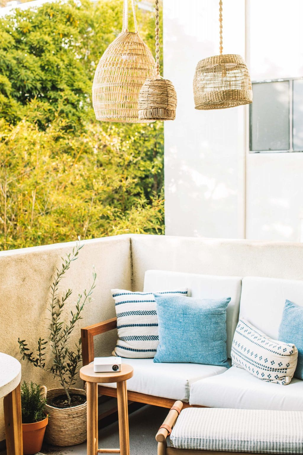 Lanterns hanging over an outdoor love seat with a small stool with a projector on it.