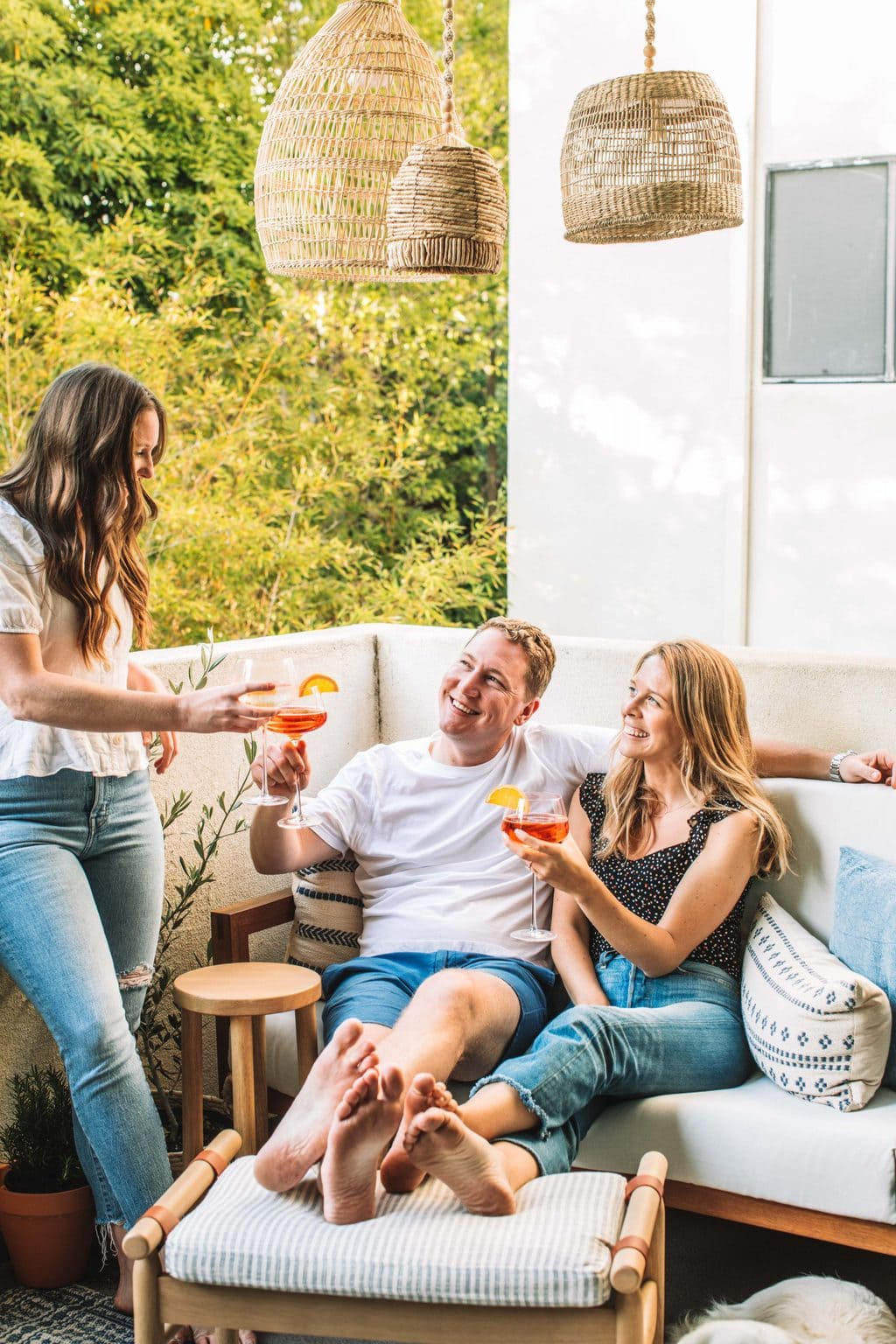 Three people enjoying a lounge space on a love seat and a footstool having a cocktail.