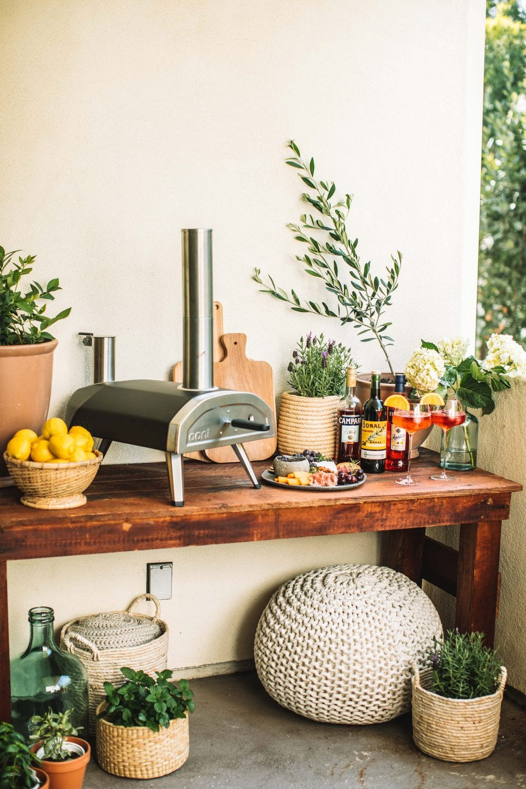 A wood fired oven pizza table decorated with baskets, planters, cocktail glasses, and a cheeseboard.