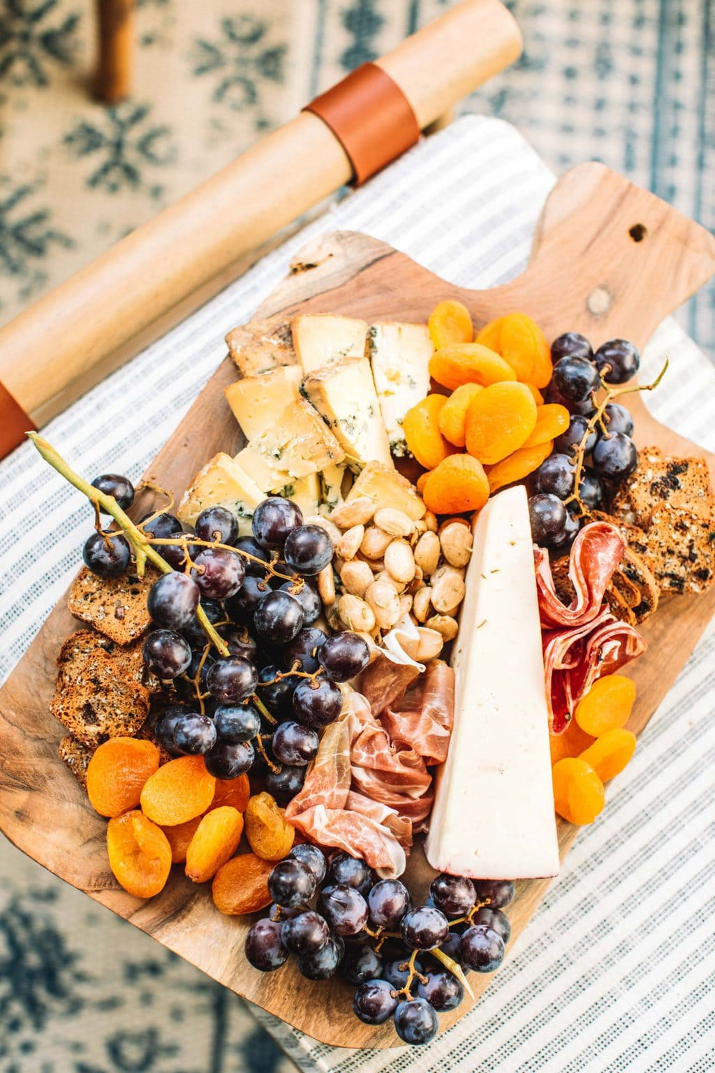 A cheeseboard on a wooden platter sitting on fabric foot stool.