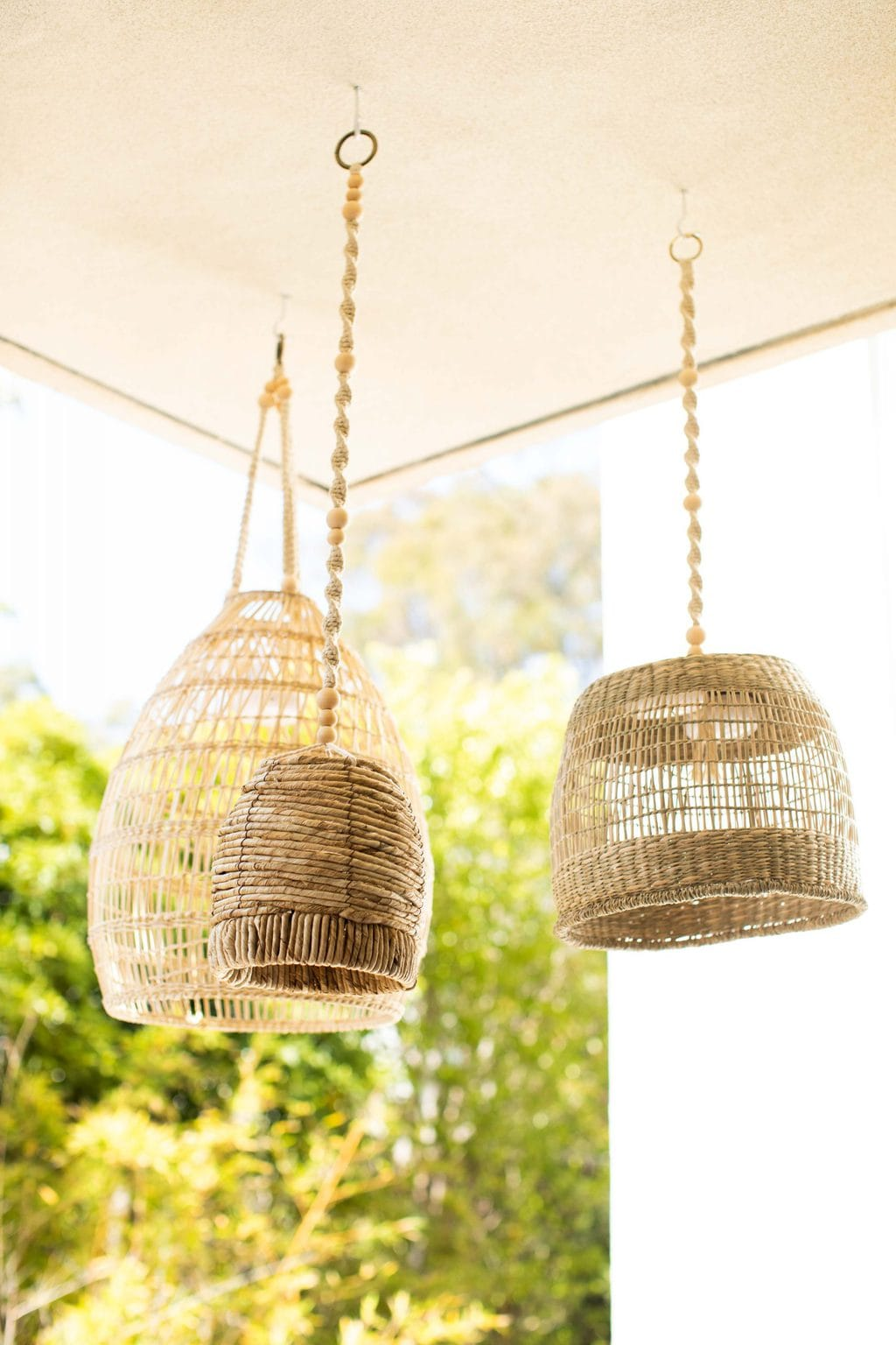 DIY Wireless Basket Lanterns hanging from an eye hook in the ceiling.