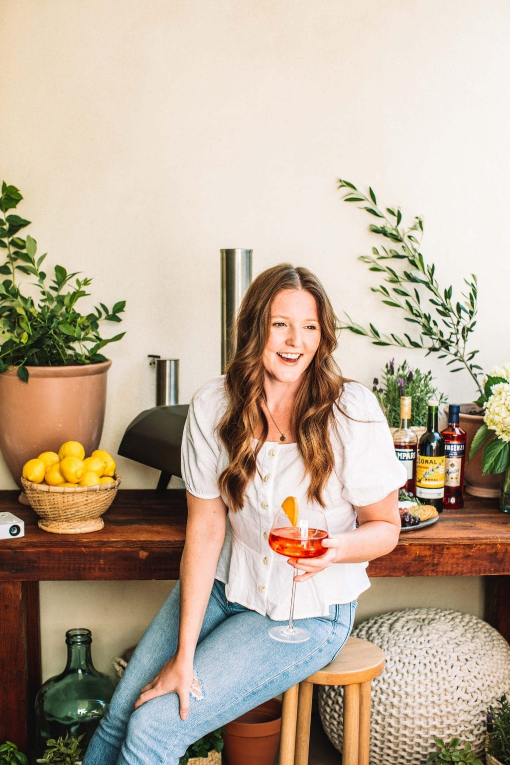 A girl sitting on a stool holding an aperol spritz.