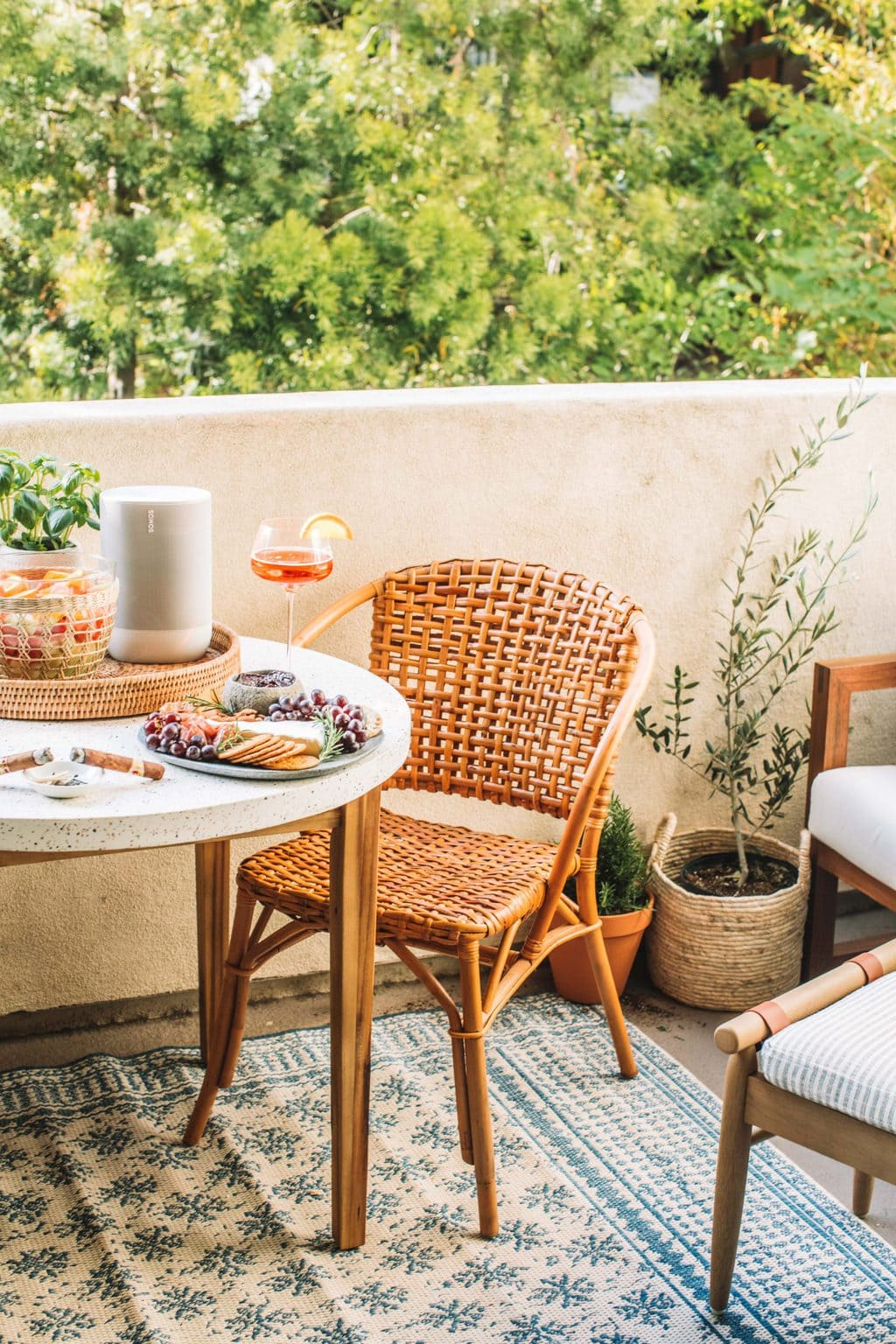 A round dining table with a cheese board and an aperol spritz on top.