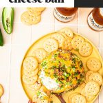 cheese ball on yellow platter with round crackers
