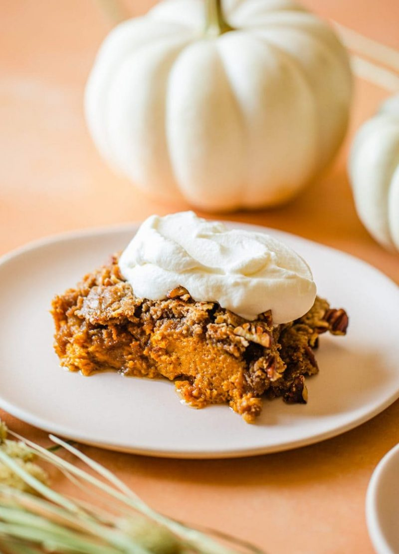 a slice of pumpkin dump cake topped with whip cream