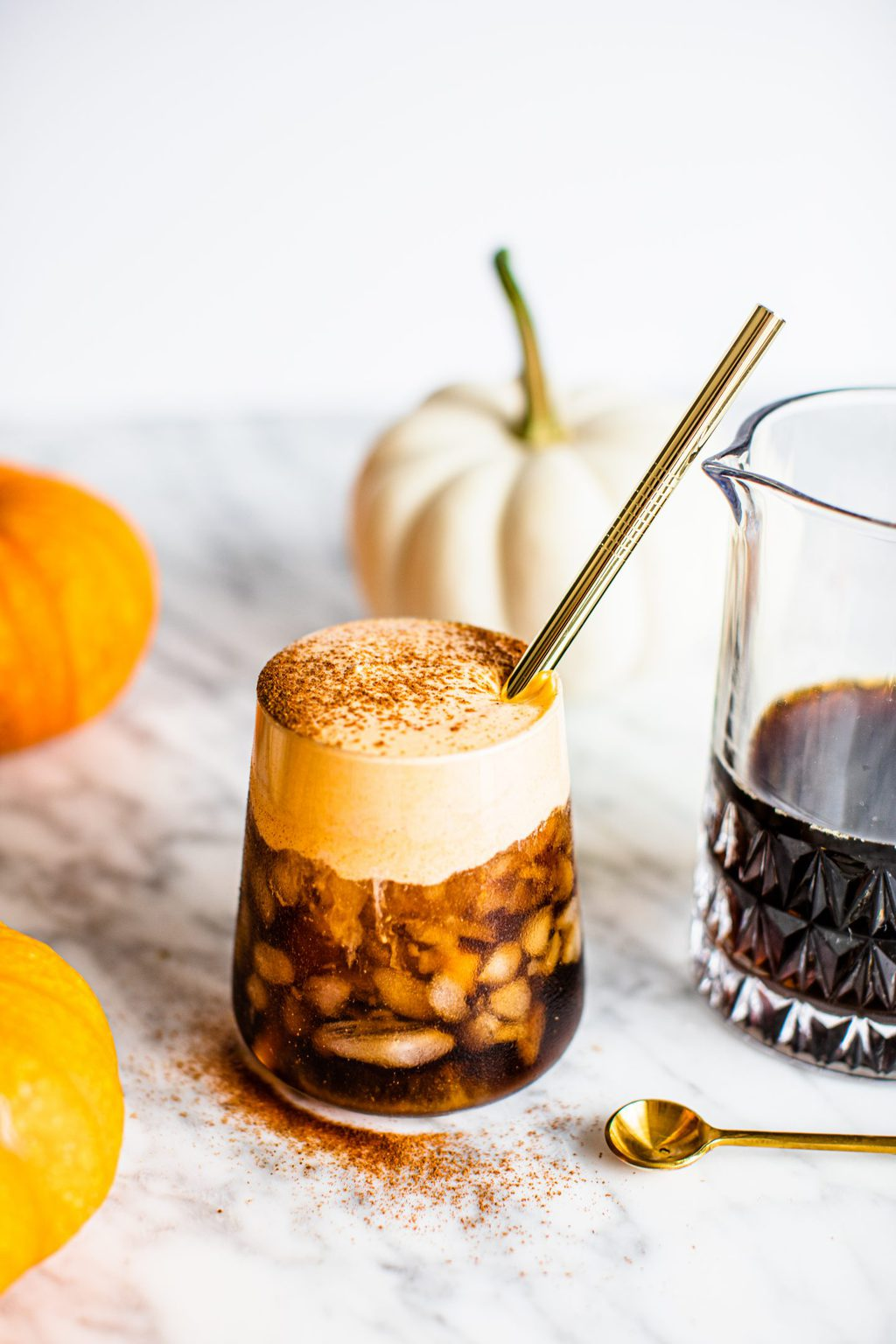 pumpkin cold brew in glass with gold straw