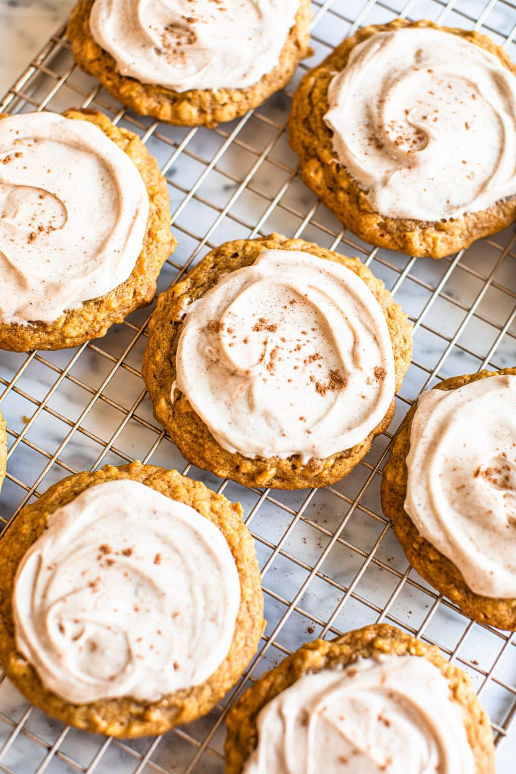 pumpkin oat cookies with icing on cooling rack