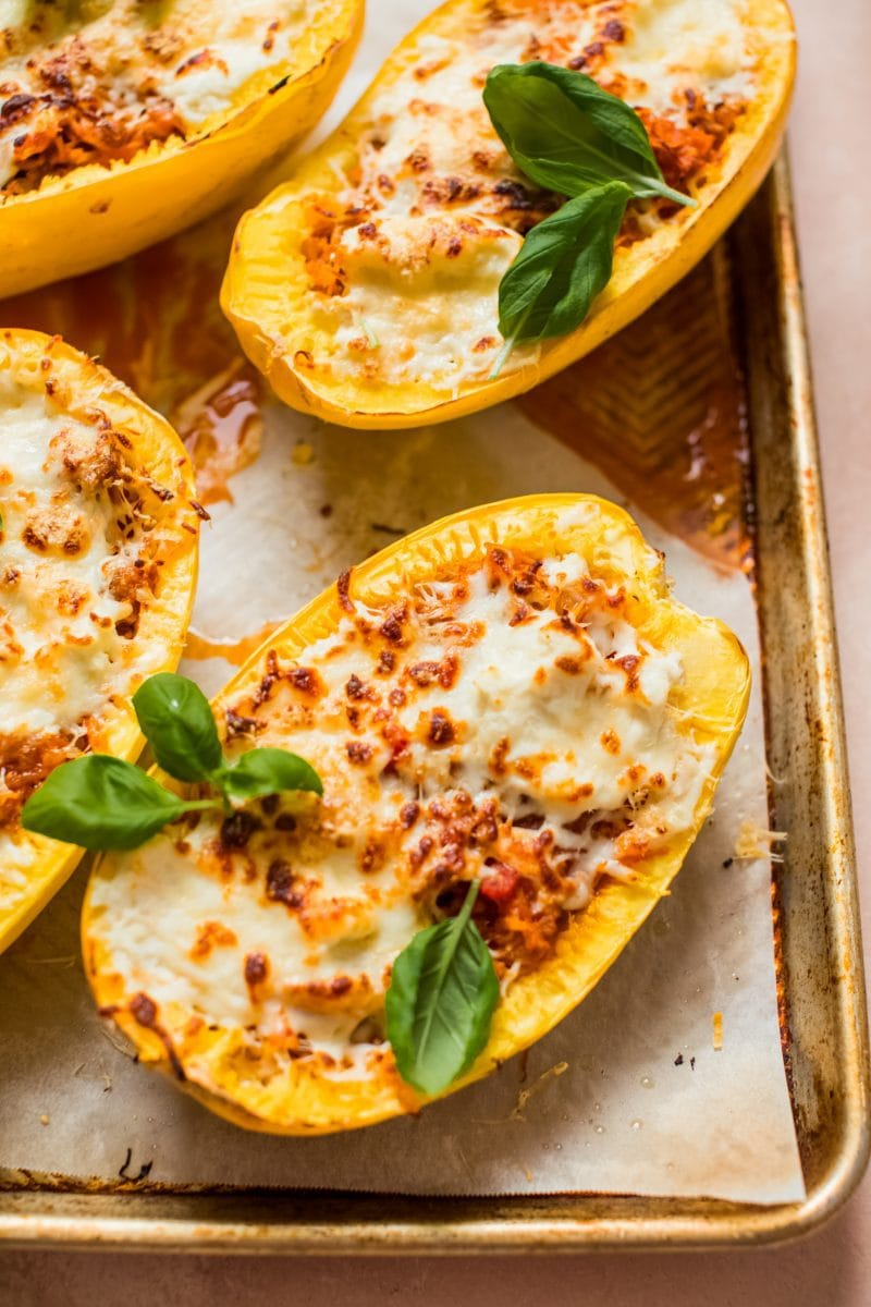 spaghetti squash halves filled with meat, sauce and cheese on baking sheet