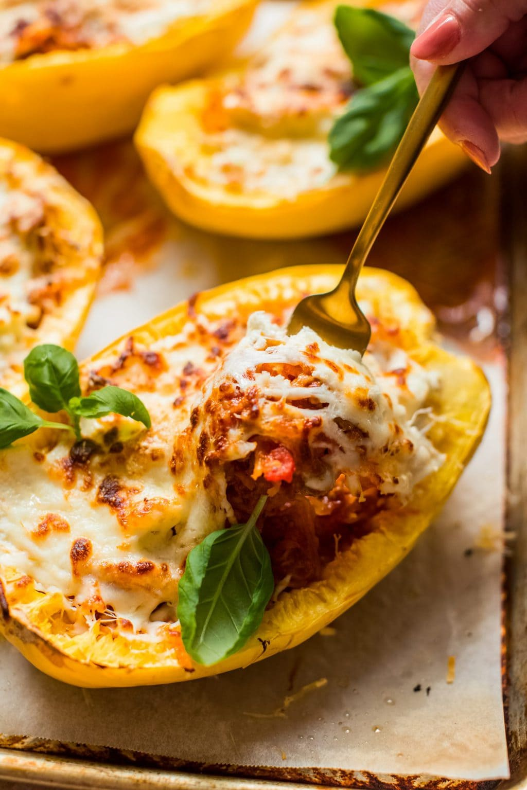 fork digging into spaghetti squash half filled with meat, sauce and cheese