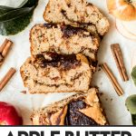 sliced apple loaf cake with cinnamon sticks and apples